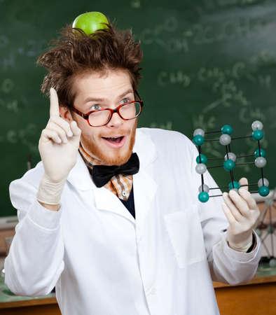 investigador cientifico: Científico loco con una manzana verde en la cabeza muestra el dedo índice mientras entregaba modelo molecular