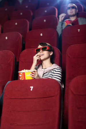 theater popcorn: Young woman with popcorn in 3D movie Stock Photo