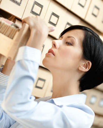 seeks: Woman seeks something in card catalog composed of set of wood boxes at the library. Information
