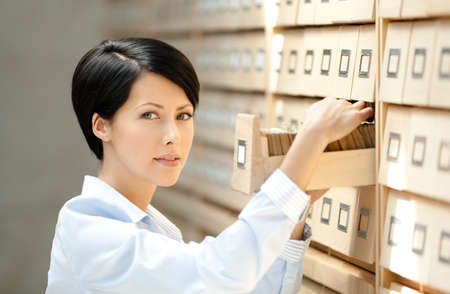 Pretty woman searches something in card catalog composed of set of wood boxes at the library. Knowledge Stock Photo - 15316200