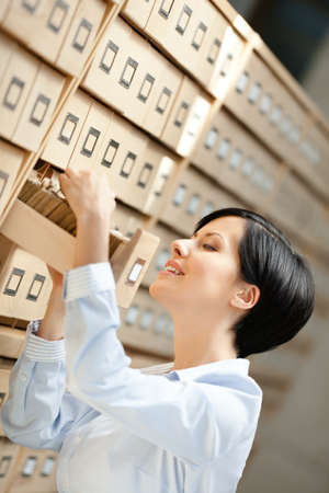seeks: Woman seeks something in card catalog composed of set of wood boxes at the library. Studying Stock Photo