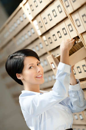 Woman looks for something in card catalog composed of set of wood boxes at the library. Knowledge photo