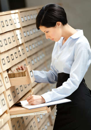 suit skirt: Woman searches something in card catalog composed of set of wood boxes at the library. Studying