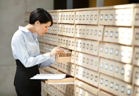 Woman seeks something in card catalog composed of set of wood boxes at the library. Knowledge photo