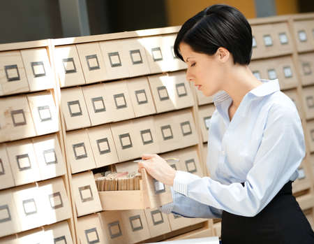 Woman seeks something in card catalog composed of set of wood boxes at the library. Education and research photo