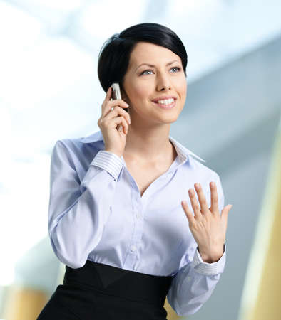 short skirt: Business woman in business suit talks on telephone. Leadership