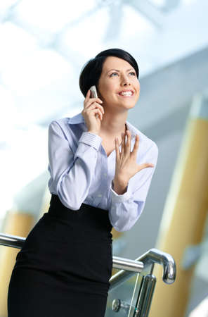 Business woman in business suit talks on cellular phone. Leadership photo