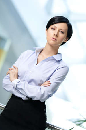 Portrait of a handsome successful businesswoman wearing white shirt and black skirt at business centre photo