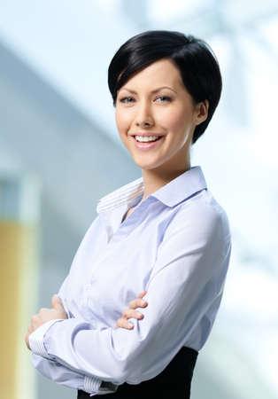 короткие волосы: Портрет красивый успешная деловая женщина носить белую рубашку и черную юбку в бизнес-центре Фото со стока
