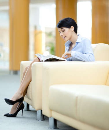 Woman rests at the sofa reading book at the hall photo