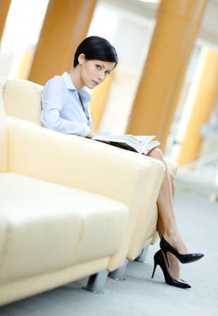 Business woman rests at the sofa reading professional literature at the hall photo