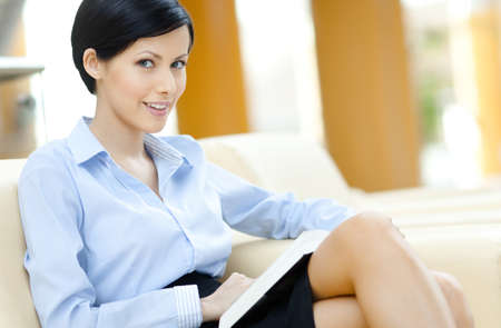 Business woman rests at the white leather sofa with book at the hall
