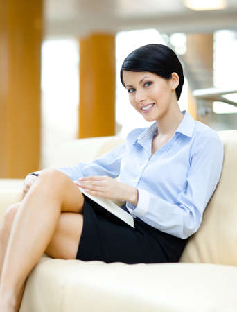 skirt suit: Successful young business woman rests at the sofa reading book at the hall Stock Photo