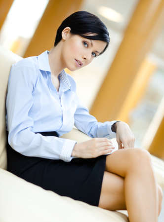 skirt suit: Business woman rests at the sofa handing book at the hall