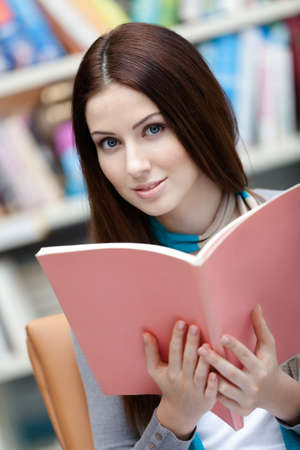 browses: Female student browses the book at the library. Education