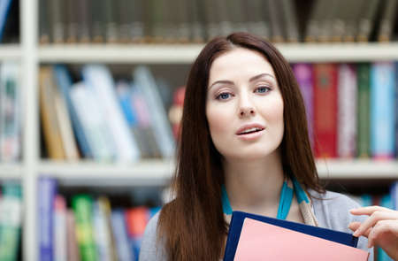 Beautiful female student with books at the library. Research. Learning Stock Photo - 15316317
