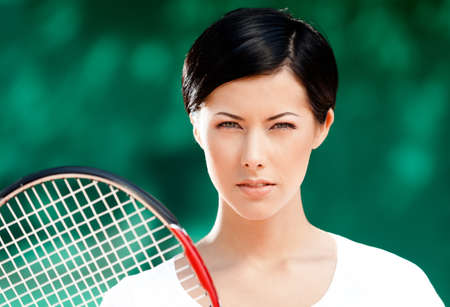 Portrait of successful female tennis player with racket at the tennis court photo