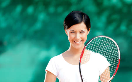 Portrait of female tennis player with racket at the tennis court. Outdoors photo