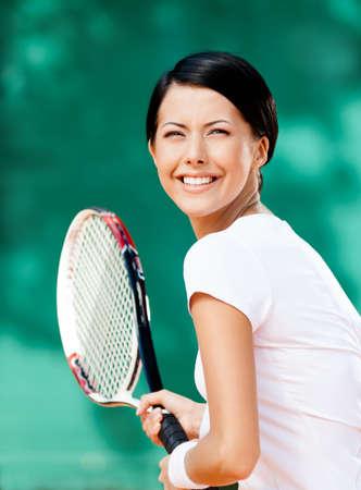 mujer deportista: Retrato del jugador de tenis con la raqueta bastante en la pista de tenis