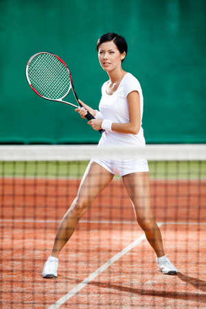 Sportswoman at the tennis court with racquet. Tournament photo