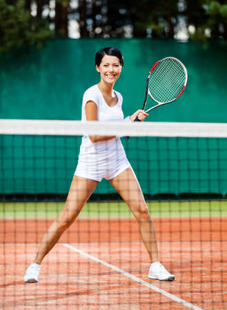 Sportswoman at the tennis court with racquet. Contest photo