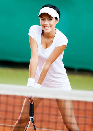 Sportswoman at the tennis court with racquet. Competition