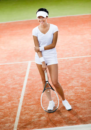 athletic wear: Woman in sportswear with tennis racket at the tennis court Stock Photo