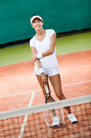 Sporty woman in sportswear with tennis racket at the tennis court photo