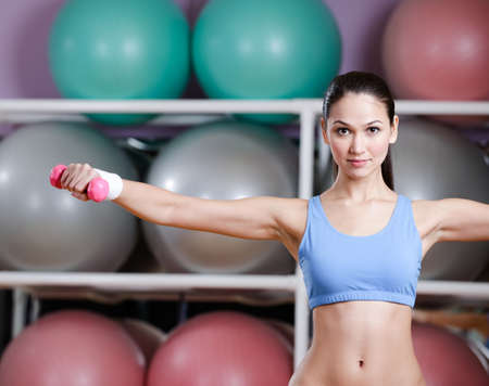 Physically strong woman training with dumbbells in gym photo