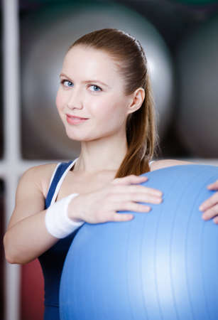 keep fit: Woman with blue gym ball in fitness gym Stock Photo
