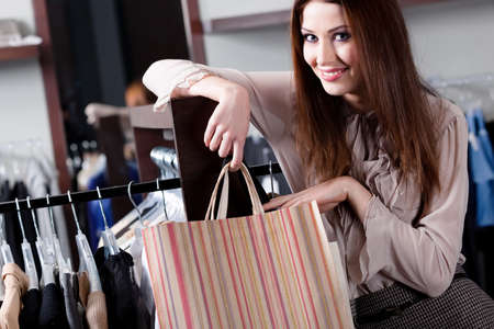 carries: Smiling woman carries paper bags at the store