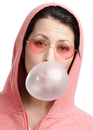 Woman in sweatshirt and heart shaped glasses blows out pink bubble gum, isolated on white photo