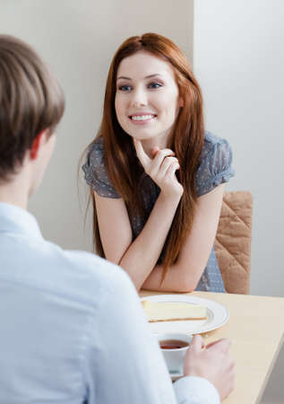 Woman talks with man sitting at the table at the bar photo