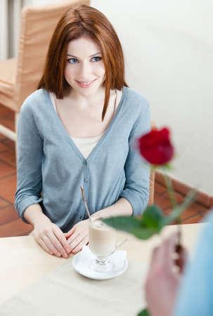 faire l amour: L'homme pr�sente une rose rouge � sa petite amie au caf� Banque d'images