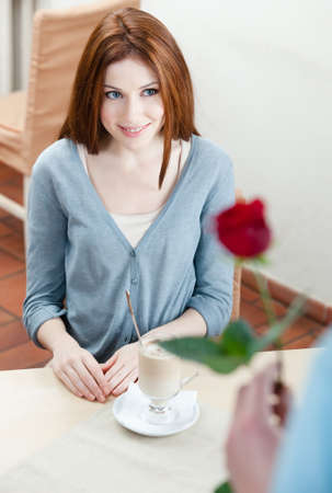 Man presents a red rose to his girlfriend at the cafe photo