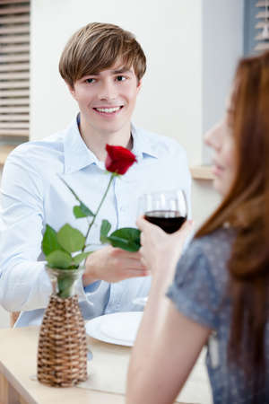 Couple is at the coffee house sitting at the table with vase and scarlet rose in it photo
