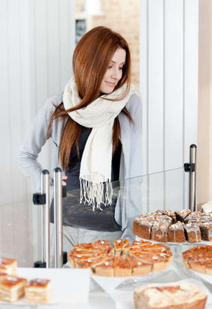 Woman in scarf looking at the bakery showcase full of different pieces of cakes photo