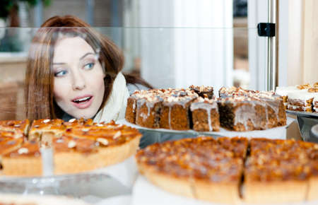 Woman in scarf looking at the bakery glass case full of different pieces of cakes photo