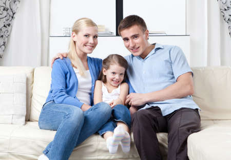family sofa: Family of three hug each other on the white leather sofa