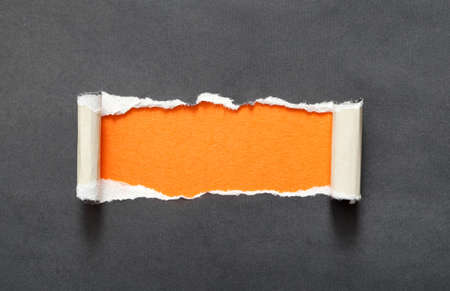 Torn black paper with orange copyspace for your message photo
