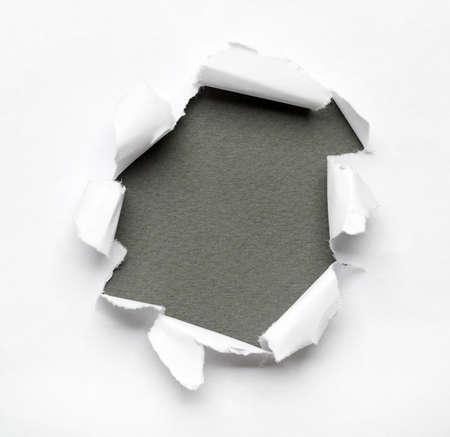 gescheurd papier: Grijze cirkel vorm doorbraak papier gat met een witte achtergrond Stockfoto