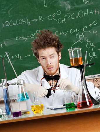 Mad professor wipes his spectacles while working in his laboratory Stock Photo - 15433446