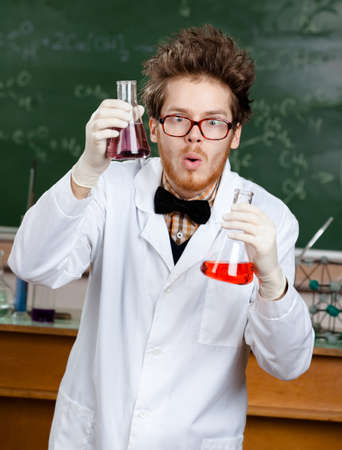 Mad scientist shows two flasks with colored liquid in his laboratory photo