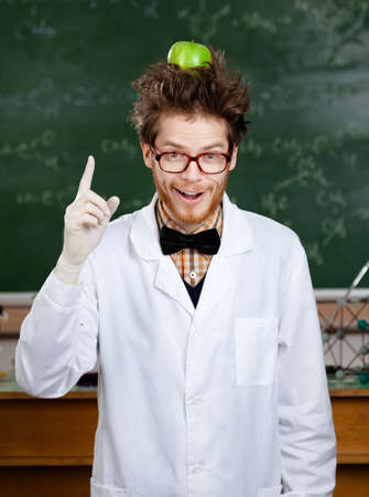 Mad scientist with a green apple on his head shows forefinger photo