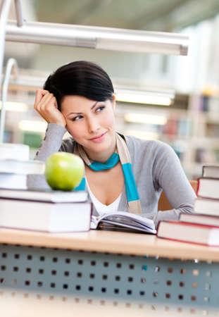 Estudiante soñadora con manzana verde estudios en la sala de lectura de la biblioteca. Educación Foto de archivo - 15435118