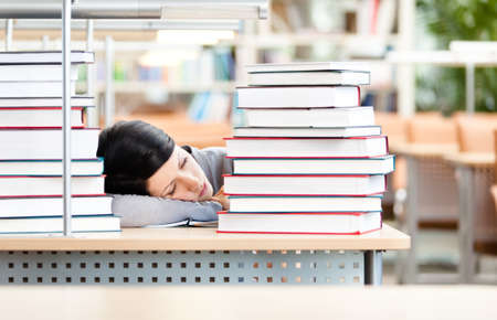 Female student sleeping at the desk with piles of books. Tired of education. photo
