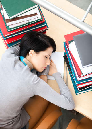 Female student sleeping at the desk with piles of books. Tired of learning. Top view photo