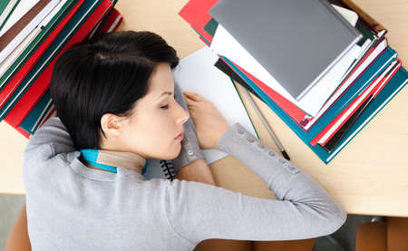 Female student sleeping at the desk with piles of books. Tired of training. Top view Stock Photo - 15433512