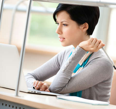 adult learning: Woman studying on the laptop at the reading hall Stock Photo