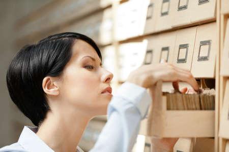 Mujer busca algo en el catálogo de fichas compuesto de un conjunto de cajas de madera en la biblioteca. Aprendizaje